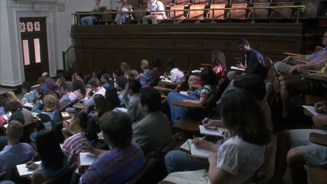 wide angle on a lecture hall filled with students. camera pans from r-l towards the front of the class with human anatomy posters posted on chalkboard. - ivy league university stock videos and b-roll footage