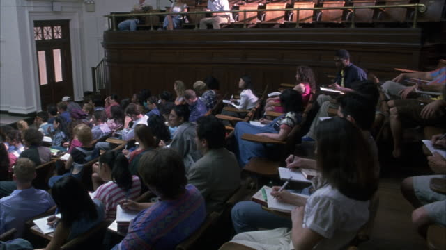 WIDE ANGLE ON A LECTURE HALL FILLED WITH STUDENTS. CAMERA PANS FROM R-L TOWARDS THE FRONT OF THE CLASS WITH HUMAN ANATOMY POSTERS POSTED ON THE BLACK BOARD.