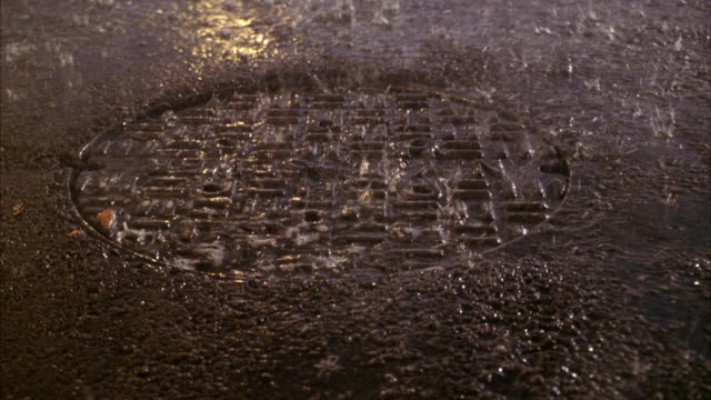 CLOSE ANGLE OF MANHOLE IN MIDDLE OF STREET. SEE RAIN POURING DOWN.