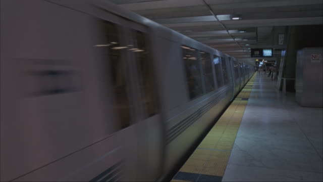 vídeos de stock e filmes b-roll de medium angle of bart train station. see train or subway waiting at platform to left. see bart ba on sides of train. see train begin to move past pov. camera pans around empty station once train leaves. - plataforma de estação de metro