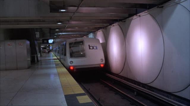 vídeos y material grabado en eventos de stock de medium angle looking down tracks on platform in indoor train station. see bart train or subway on right moving away from pov. - bart