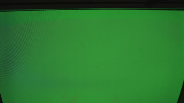 vídeos de stock, filmes e b-roll de pull back from television monitor screen to reveal control panel and other tv monitors. green screen showing on center monitor. could be spying or surveillance. - 2007