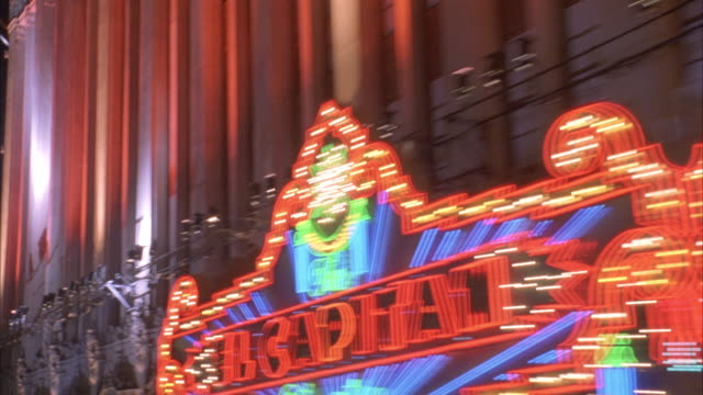 pan l-r along el capitan theatre and storefronts. signs lit up at night. nightlife. hollywood blvd. movie theaters. spotlights shine on wall. could be movie premiere. - el capitan theatre stock videos & royalty-free footage