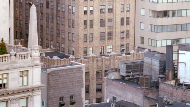 high angle down of several office buildings or apartment buildings. see building at center with ornately carved border along top. - 1995 stock-videos und b-roll-filmmaterial