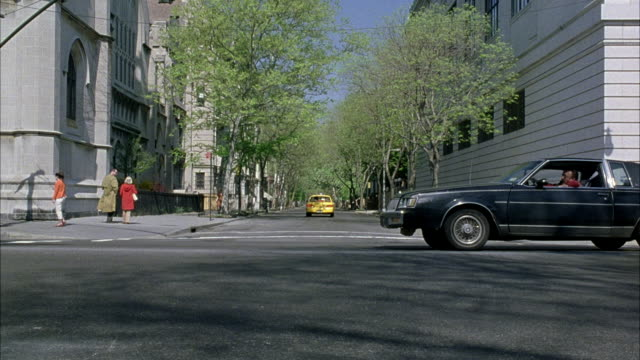 WIDE ANGLE OF INTERSECTION AS YELLOW TAXI CABS DRIVE BY. TAXI DRIVES IN REVERSE FROM BACKGROUND INTO FOREGROUND IN MIDDLE OF INTERSECTION. HIGH RISE APARTMENT BUILDINGS SURROUNDING.