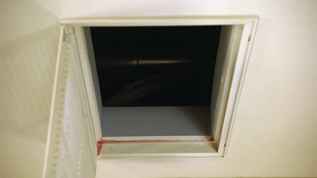 medium angle of attic opening in ceiling. attic door is hanging open. could be in a house, hotel, office, or apartment. - attic stock videos and b-roll footage