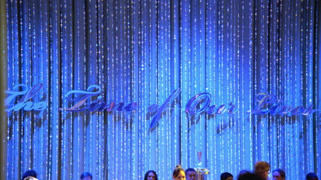 wide angle of ballroom or auditorium decorated for celebration or party or prom. the time of our lives banner hangs in the bg. lights change and confetti falls. - ballroom stock videos & royalty-free footage