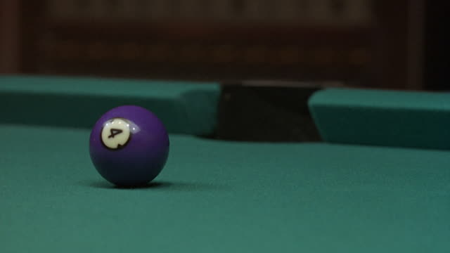CLOSE ANGLE OF POOL TABLE WITH SOLID, FOUR BALL. CUE BALL COMES FROM RIGHT AND KNOCKS BALL INTO POCKET. CUE BALL EXITS LEFT, THEN COMES BACK IN AT END FROM LEFT AND EXITS RIGHT. INSERT.