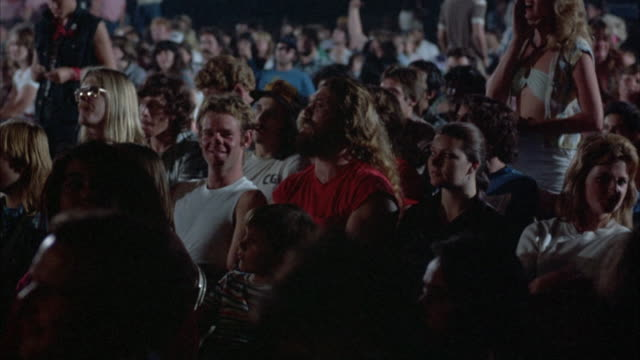 medium angle. young rock concert audience dressed in early 1980's attire sitting quietly in chairs, talking amongst themselves, and waiting for concert to begin. - audience stock videos & royalty-free footage