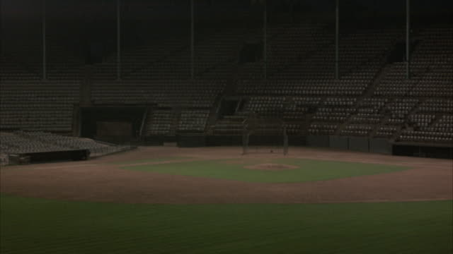 wide angle of baseball field, with 1940's period stadium seats seen surrounding field. shot begins in blackness with stadium lighting gradually coming on and revealing the field and stadium seating area. neg cut. - baseball diamond stock videos and b-roll footage