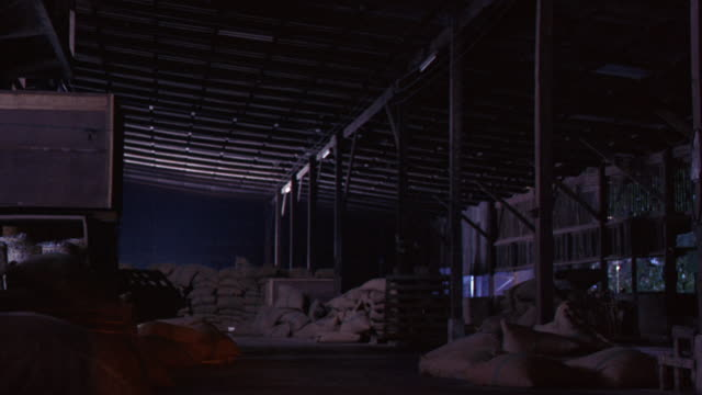 wide angle of a large storage barn or warehouse interior at night. see burlap bags stacked. see several large wooden poles from ground to ceiling. wooden crate leaning against pole. - barn stock videos & royalty-free footage