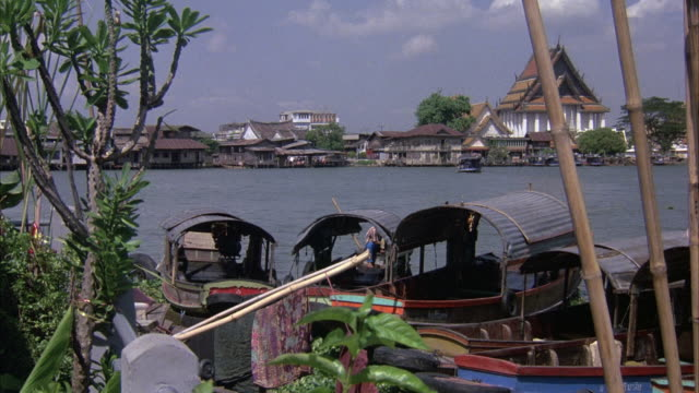 medium angle of boats in chao phraya river. see river and houses on river in background. see white temple in right background. see boat begin to enter screen on left. - bangkok stock-videos und b-roll-filmmaterial