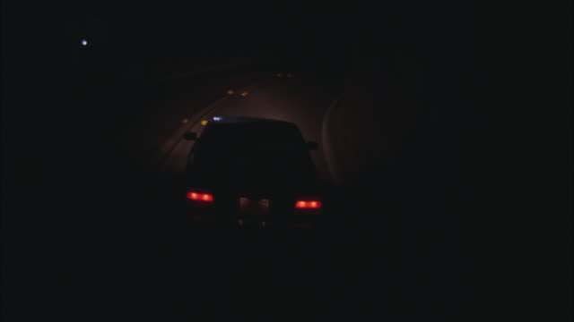 TRACKING SHOT OF BMW CAR ON COUNTRY ROAD. HEADLIGHTS ARE ON. CAR IS SWERVING ACROSS BOTH LANES OF ROAD.