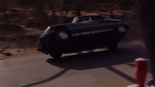 TRACKING SHOT OF CITROEN DS 21 CAR DRIVING ON SIDE TWO WHEELS WHILE 1985 BMW 520I SEDAN DRIVES ALONGSIDE. CITROEN LANDS BACK ON FOUR WHEELS AND CARS BUMP INTO EACH OTHER. CAR CHASES AND STUNTS.
