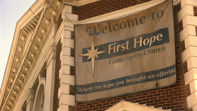 UP ANGLE OF BANNER HANGING ON CORNER OF BRICK BUILDING THAT READS WELCOME TO FIRST HOPE COMMUNITY CHURCH, WHERE WE HOPE YOU BROUGHT AN OFFERING. CHURCH, COMMUNITY CENTER, OR RELIGIOUS BUILDING
