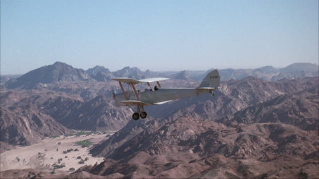 medium angle of small single propeller biplane flying over rocky, jagged desert mountains. - propeller stock videos and b-roll footage