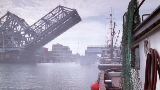 medium angle of drawbridge up above river or body of water. see overcast above water surface, boat approaches front behind drawbridge. see tugboats in right foreground. - drawbridge stock videos and b-roll footage