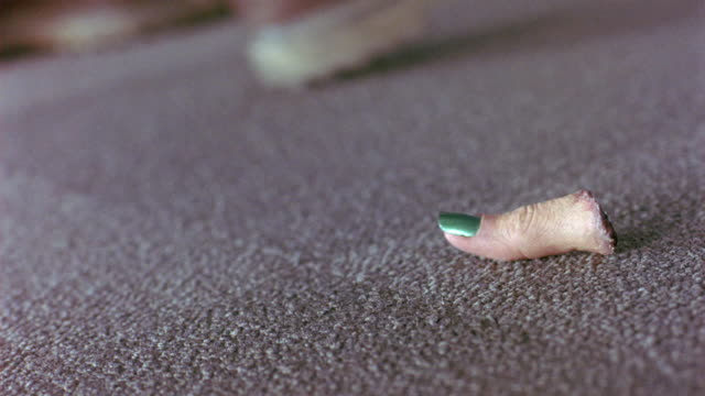MEDIUM ANGLE OF GRAY CARPET ON GROUND. SEE SINGLE SEVERED FINGER FALL TO GROUND AND LAND ON CARPET SEE GREEN FINGER NAIL POLISH ON NAIL. SEE SHOE OR BOOT OF MAN STEP INTO FRAME AT VARIOUS POINTS. HAND PICKS UP FINGER AND DROPS IT AGAIN.
