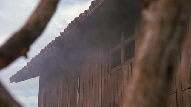 medium angle of stunt of man falling out second story window of wooden building. could be barn. see man break wooden frame of window and fall to stack of hay or grass. - hay stack stock videos & royalty-free footage