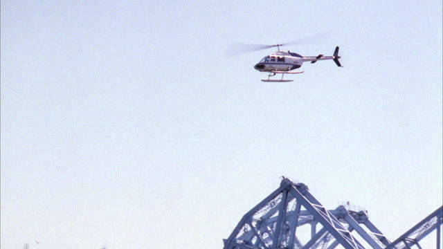 medium up angle of helicopter spinning in circles. see drawbridge on right and buildings on left. - drawbridge stock videos and b-roll footage