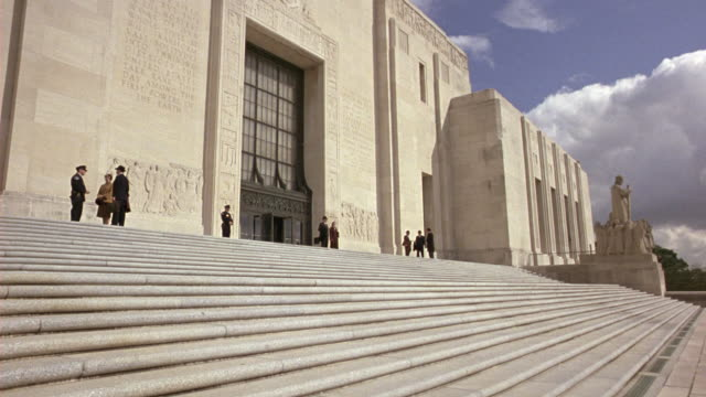medium angle of the steps outside the louisiana state capitol building in baton rouge.  men in suits stand and walk on the steps.  police officers stand guard and give directions.  the art deco skyscraper towers above. government buildings. - baton rouge stock-videos und b-roll-filmmaterial