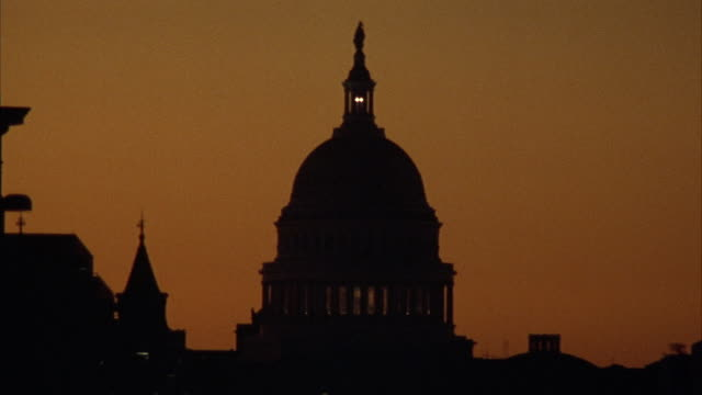 ESTABLISHED MEDIUM ANGLE OF CAPITOL BUILDING AT SUNSET. SEE SILHOUETTE OF OTHER BUILDINGS, SKY HAS TINT OF ORANGE.