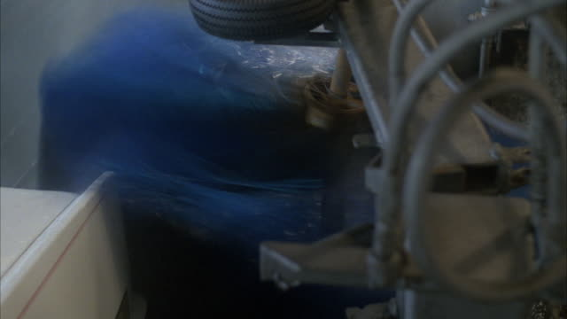 close angle of car wash brush spinning. see white cadillac sedan pass through car wash as spinning brush washes side. - キャデラック点の映像素材/bロール