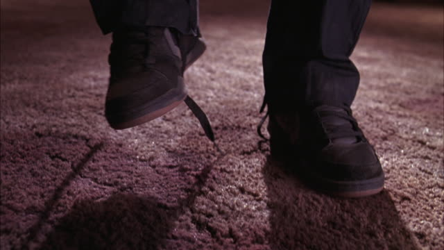 close angle of man's shoes and legs standing on carpet in lower class motel or hotel. shoe laces are untied. - untied stock videos and b-roll footage