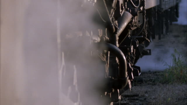 close angle shot of steam locomotive train engine undercarriage. steam is seen venting from area. - anno 1923 video stock e b–roll