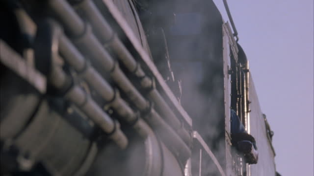 close angle of train undercarriage with steam coming from beneath. sky looks overcast. - anno 1923 video stock e b–roll
