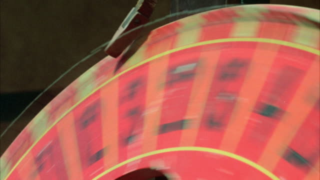 close angle shot of hand spinning a worn-looking carnival game wheel. see only top part of wheel. lands on number eight. could be a casino money wheel. - anno 1923 video stock e b–roll