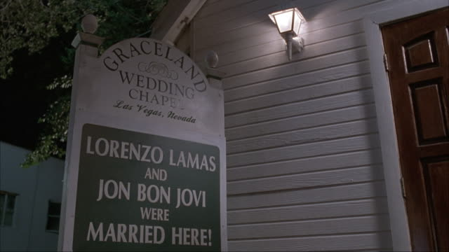medium angle of entrance to wedding chapel with sign that reads graceland wedding chapel - lorenzo lamas and jon bon jovi were married here. matching night shot from same production. - chapel stock videos & royalty-free footage