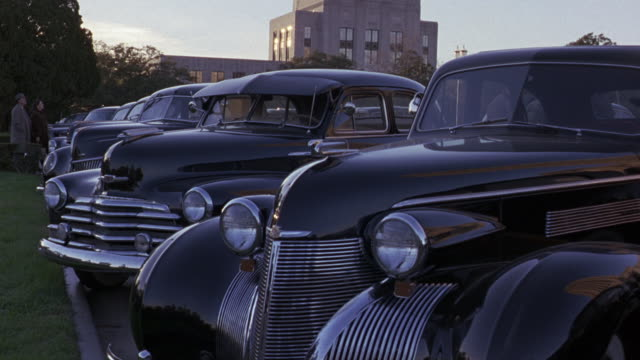medium angle of a row of classic cars. a chevy and a dodge or maybe a chrysler.  the louisiana state capitol building in the background.  a few people in period clothes walk through the parked cars. chevrolets. - kapitol von louisiana stock-videos und b-roll-filmmaterial