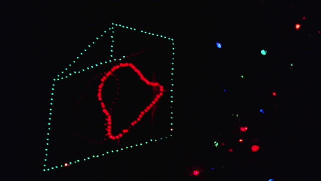 CLOSE ANGLE OF CHRISTMAS LIGHTS WITH DECORATION OF PAIR OF FLASHING RED BELLS IN GREEN HOUSE-SHAPED LIGHTS. NEG CUT.