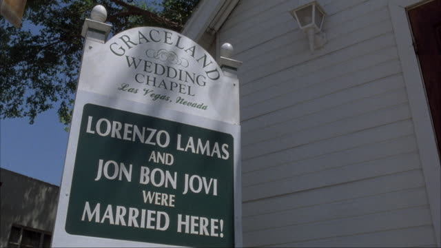 medium angle of entrance to wedding chapel with sign that reads graceland wedding chapel - lorenzo lamas and jon bon jovi were married here. matching day shot from same production. - chapel stock videos & royalty-free footage