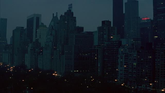 vídeos de stock, filmes e b-roll de 3/4 side medium angle of partial new york city skyline skyscrapers lined on right. - 1980 1989