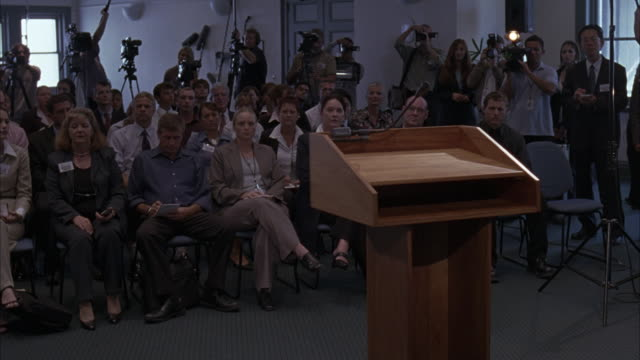 conference room or press room filled with men and women reporters sitting in chairs. people wear badges. podium with microphone in foreground. men with video cameras and still photography cameras in background. - journalist stock videos and b-roll footage