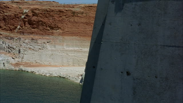 wide angle of riverbank. see red rocky cliff in background. part of glen canyon dam in foreground. - glen canyon staudamm stock-videos und b-roll-filmmaterial