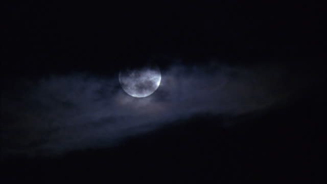 pan left to right of full moon with silhouette of clouds moving. - vollmond stock-videos und b-roll-filmmaterial