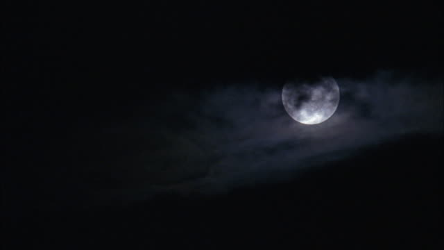 medium angle of full moon with silhouette of clouds moving. - vollmond stock-videos und b-roll-filmmaterial