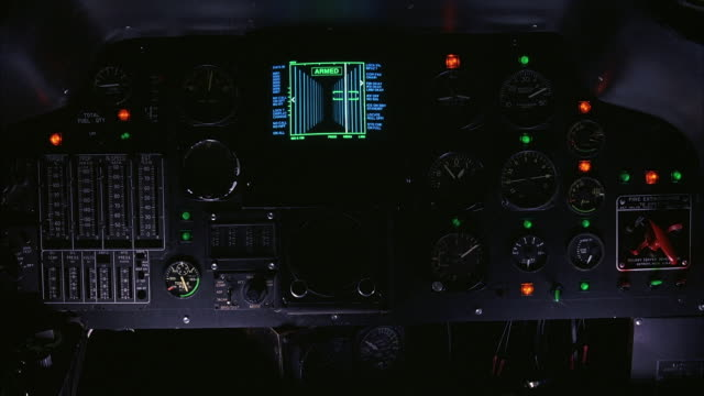 MEDIUM ANGLE OF HELICOPTER COCKPIT CONTROL PANEL WITH SEVERAL BUTTONS AND DIALS. SEE GREEN SCREEN COVERING WINDOWS OVERHEAD.