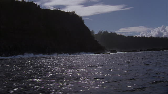 WIDE ANGLE OF ROCKY HAWAII COASTLINE FROM SLOW MOVING BOAT POV. SEE SMALL WAVES CRASH INTO ROCKS. SMALL DINGHY IN WATER AT END OF SHOT. COASTLINE IS MADE OF MOUNTAINS AND TREES. BRIGHT SUNNY DAY WITH LIGHT WISPY CLOUDS.