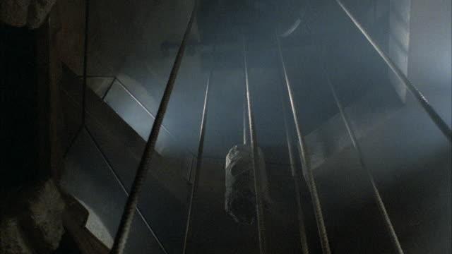 vídeos de stock e filmes b-roll de medium angle of counterweight or fly rail system used to operate church bells in bell tower. - torre estrutura construída
