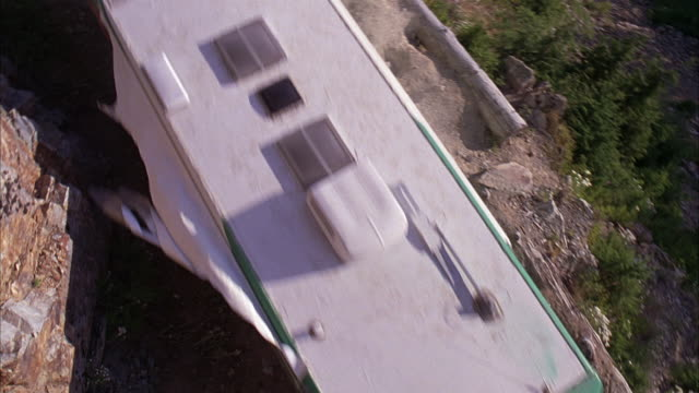 high angle down of narrow mountain road which passes fallen tree trunk. green and white rv seen driving through narrow pass. - camper van stock videos and b-roll footage