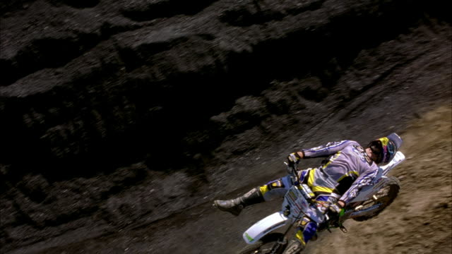 high angle down of dirt biker doing a candy bar/saran wrap. after jumping off dirt ramp. close angle as camera follows dirt biker doing stunt/trick from r-l. slow motion 120 fps. - motocross stock videos & royalty-free footage