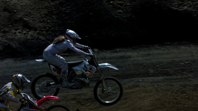MEDIUM ANGLE OF GROUP OF DIRT BIKERS RACING ON TRACK. PANS LEFT TO RIGHT FOLLOWING BIKERS. FOCUS ON BIKER WITH LONG HAIR AND WEARING SILVER. BIKER MAKES A U-TURN BACK LEFT AND JUMPS OFF HILLS. PANS LEFT TO FOLLOW BIKERS JUMPING OFF HILL.