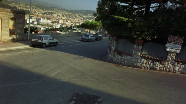 HIGH ANGLE DOWN OF SHARP RIGHT TURN OR SWITCHBACK ON WINDING ROAD OVERLOOKING URBAN AREA. INTERSECTION AND HILLSIDE. STREET SIGNS WITH FRENCH CITIES SUCH AS MONACO. EUROPE.
