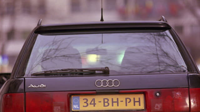 WIDE ANGLE OF THE BACK WINDSHIELD OF AN AUDI COMPACT CAR AS GUNFIRE SHOOTS THROUGH THE GLASS AND BRAKE LIGHTS. BULLET HOLES.