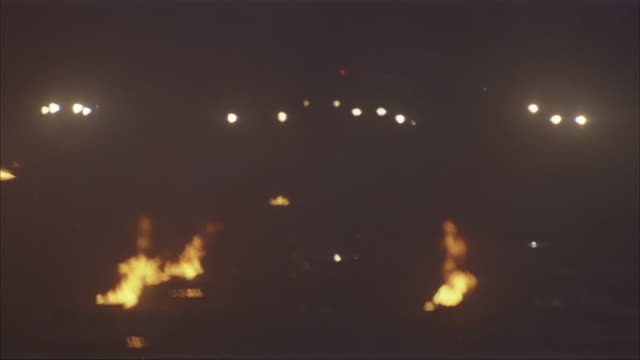 medium angle of burning wreckage. see fire next to cockpit. see cars drive up to wreckage. see fog or snow. - flugzeugabsturz stock-videos und b-roll-filmmaterial