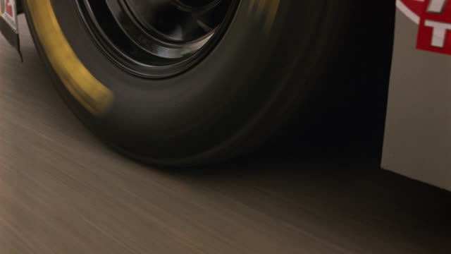 CLOSE ANGLE OF GOODYEAR TIRE ON RACE CAR TURNING AS IT MOVES AROUND RACETRACK OR SPEEDWAY. TIRE BLOWS AND GOES FLAT. CAR SKIDS, BUMPS ALONG THEN STOPS. RACING.